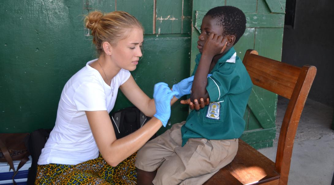 A volunteer runs a health check to a young boy in Ghana during her medicine project with Projects Abroad in Ghana.